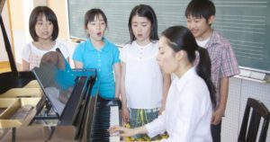 Piano teacher teaching kids to sing